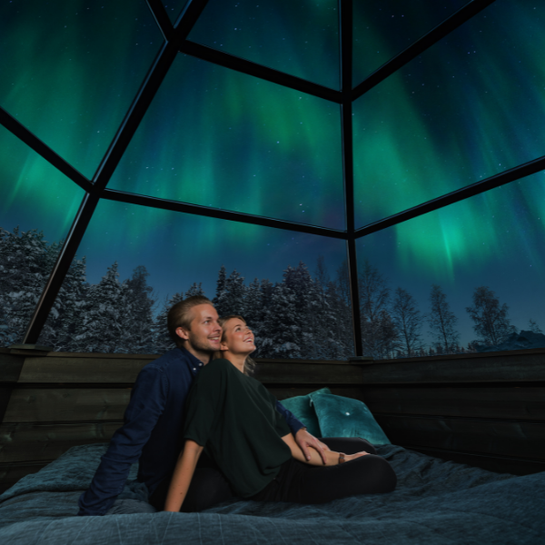 A couple admiring the Northern Lights in the glass igloo of Arctic Snowhotel and Glass Igloos in Rovaniemi Lapland Finland