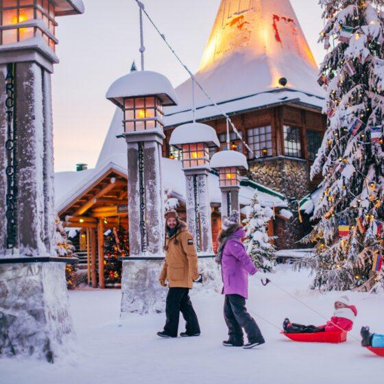 Family crossing the arctic circle in Santa Claus Village in Rovaniemi Lapland Finland
