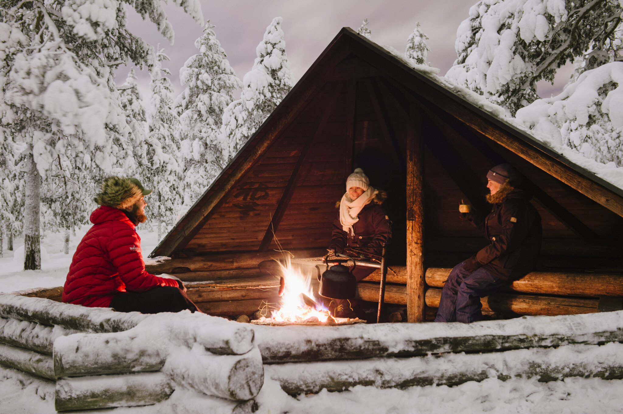 Frying Sausages by open fire in winter in Rovaniemi Lapland Finland