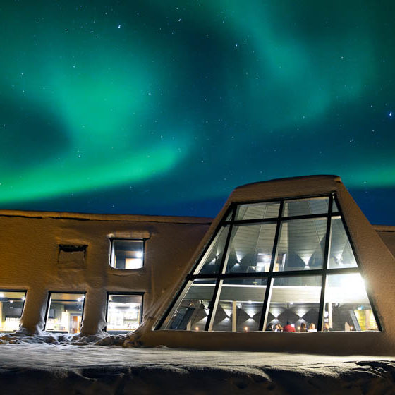 Northern Lights above Glass Resort in Santa Claus Village, Arctic Circle, Rovaniemi, Lapland, Finland