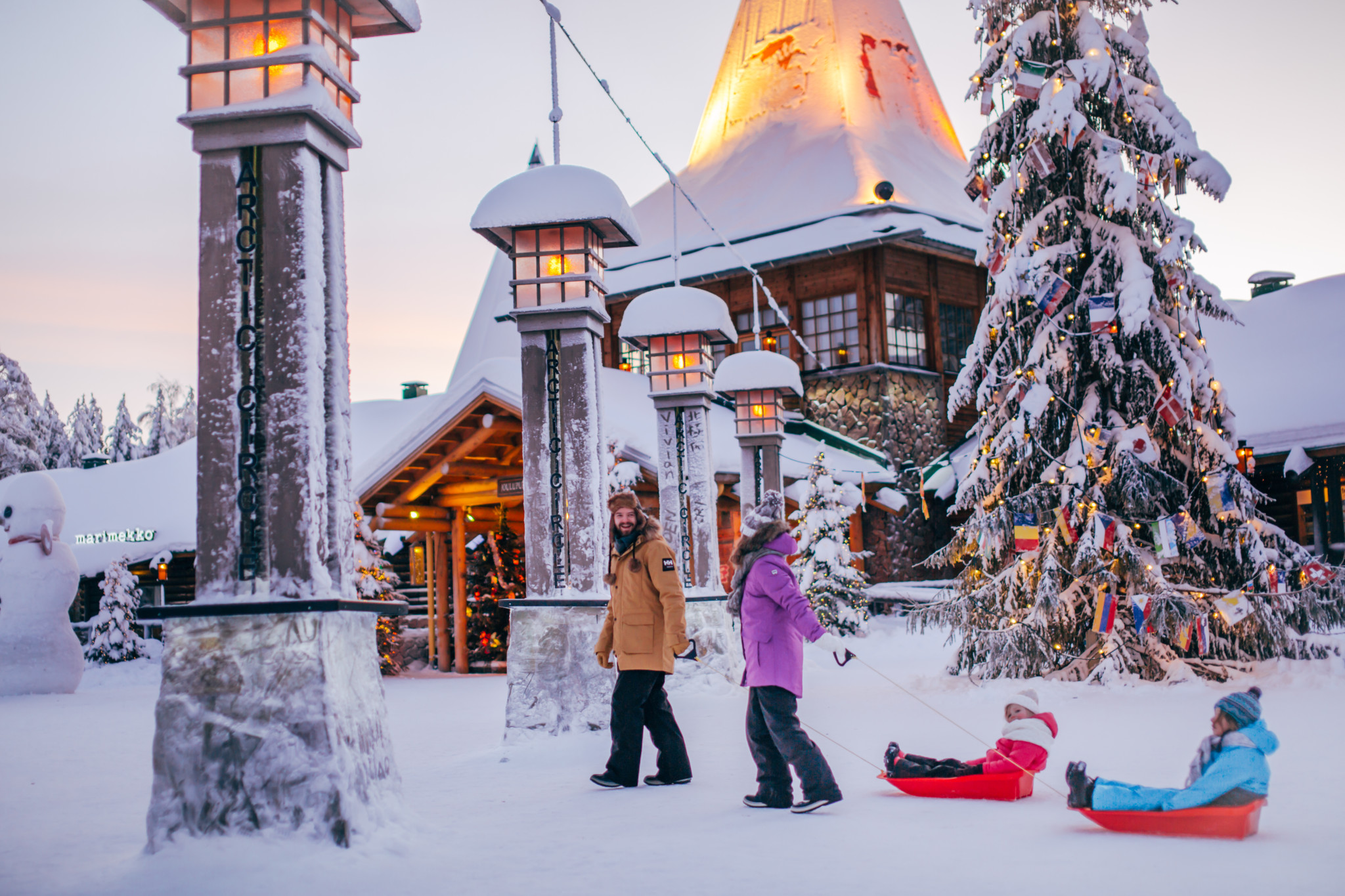 A family crossing the Arctic Circle in Santa Claus Village