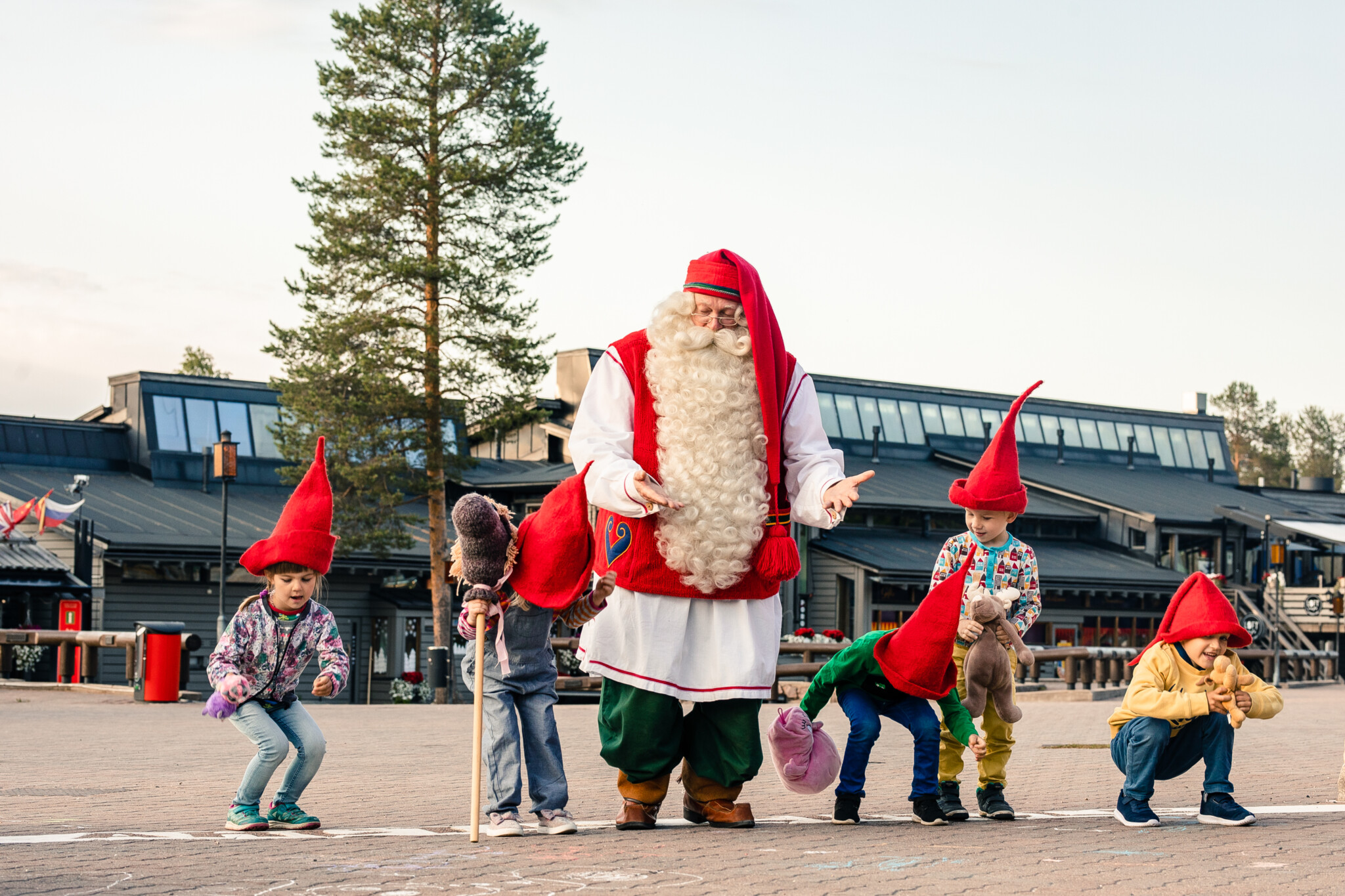 Santa Claus playing with kids on the Arctic Circle at Santa Claus Village in Rovaniemi Lapland Finland.
