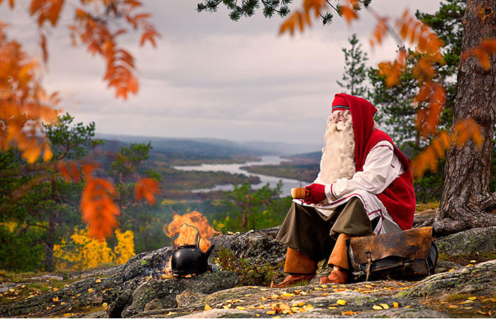 Santa Claus enjoying coffee by open fire in Rovaniemi, Lapland, Finland