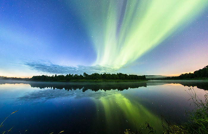 The Northern Lights blazing over water in Rovaniemi, Lapland, Finland