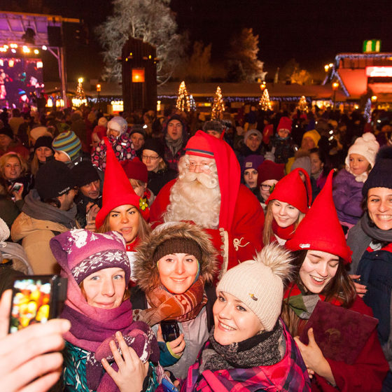 Santa Claus surrounded by people at the Grand Opening of the Christmas Season in Santa Claus Village in Rovaniemi, Lapland, Finland