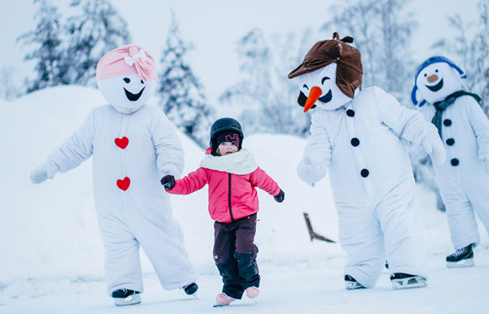 Girl ice skating with snowmen in Snowman World in Santa Claus Village in Rovaniemi, Lapland, Finland