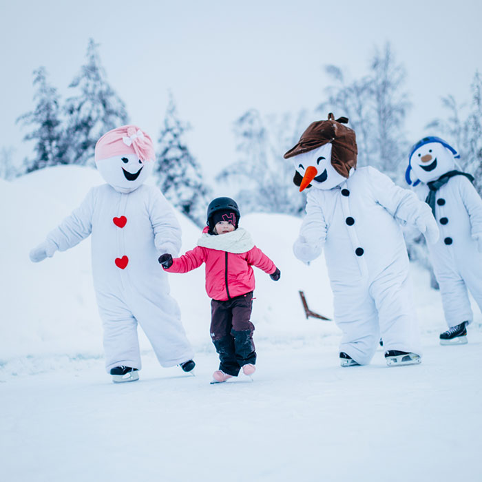 Little girl ice skating with snowmen in Santa Claus Village, Rovaniemi, Lapland, Finland