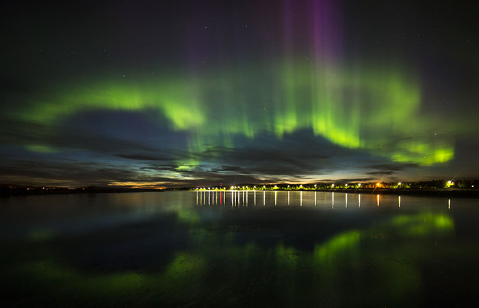 visit-rovaniemi-when-to-go-northern-lights-over-city-700x450