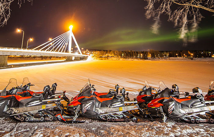 Snowmobiles under the Northern Lights ready for drivers in Rovaniemi, Lapland, Finland