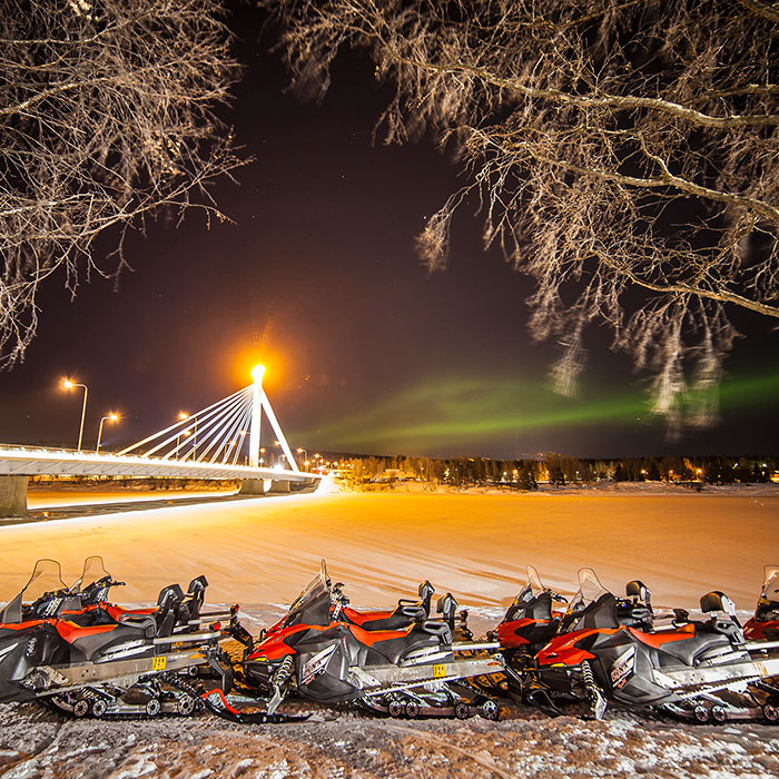 Parked snowmobiles and the Northern Lights in central Rovaniemi, Lapland, Finland