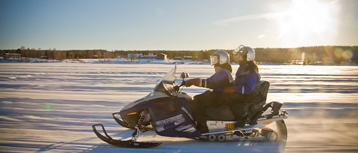 Snowmobiling on river ice by Safartica in Rovaniemi, Lapland, Finland