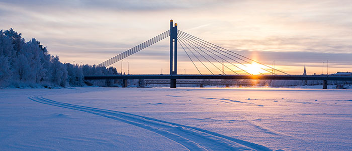 Walking in snowmobile tracks on frozen river ice in Rovaniemi, Lapland, Finland